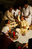 Jitendra's male relatives tie a white chord (Durga Janu) around Jitendra. This symbolizes that the groom has attained the maturity to marry.