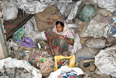 A woma sorting  plastic waste for recycling