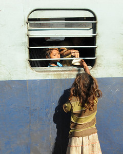 Girl begging for food from passengers on a train in Varanasi, India.