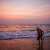 Pink sky after the sunset at Calangute beach in Goa as two boys enjoy their moment in the sea