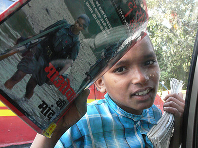 New Delhi.  Boy selling magazines while the traffic is stopped.