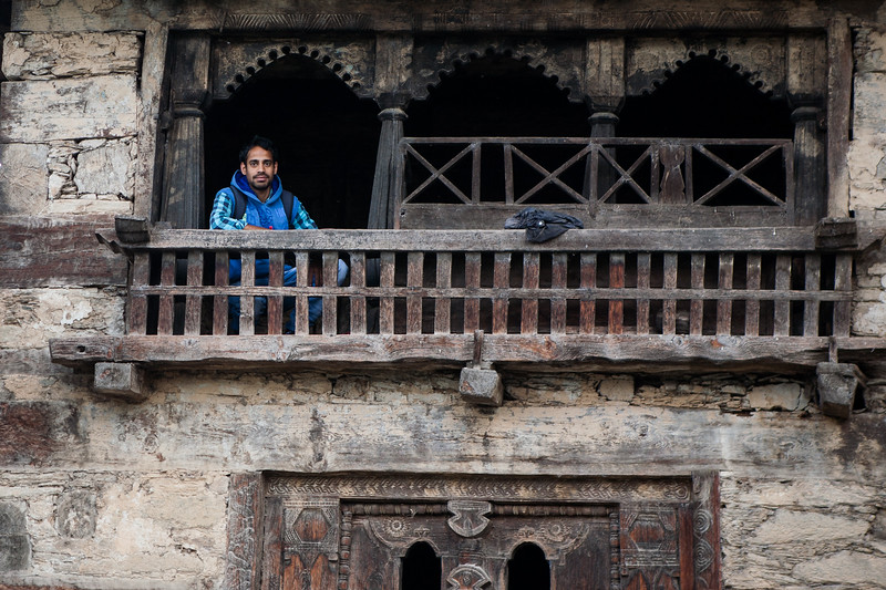 Pradeep from The Goat Village sitting in the window of an old 5-storeyed wooden house from the village Raithal