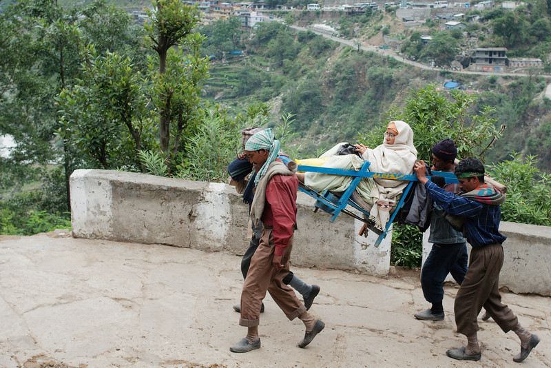 Porters carrying an elderly Sikh woman up the trail