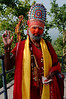 A saddhu dressed up as Hanuman receiving alms.