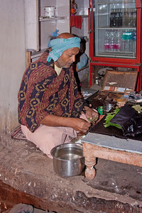 man making betel leaf, tobacco and lime rolls, India
