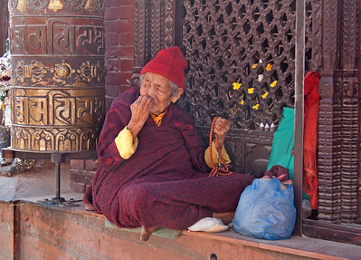 an elderly beggar next to a prayer wheel, Tibet