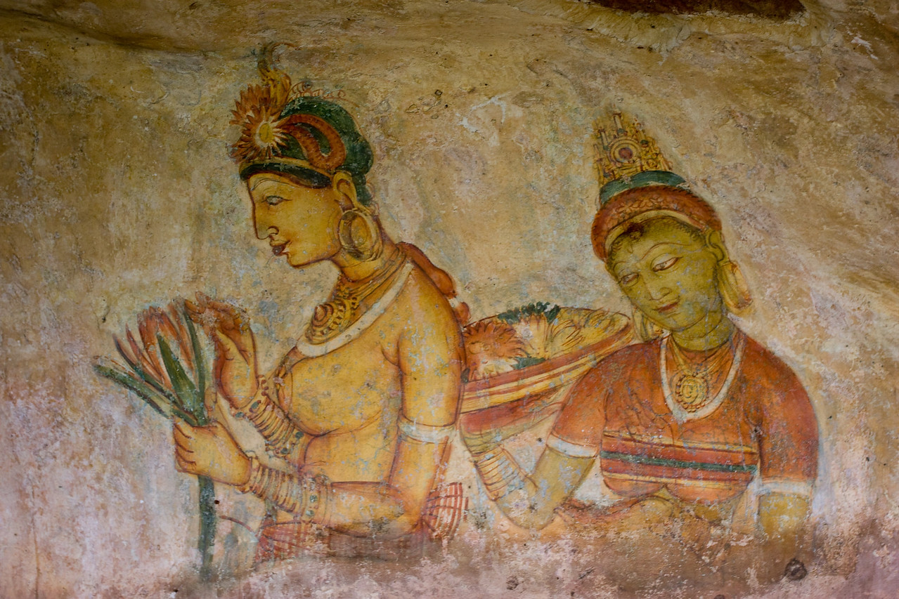 Protected from several hundred years of sun, rain, looters and vandals under an overhanging ledge half way up a several hundred foot cliff are the beautifully painted Sigiriya Maidens.  <br /> <br /> There are 12 remaining today - out of an estimated 500 that must have covered the entire cliff face in Sigiriya's heyday.  The majority of these 12 images are topless - all are busty - shown picking flowers, serving food and posing.  These maidens were painted during a thriving artistic period at Sigiriya when Europe was still in the Dark Ages.  Impressive.<br /> <br /> Picture #1 in a series of 5.<br /> <br /> Location: Sigiriya, Sri Lanka<br /> <br /> Lens used: 17-40mm f4.0