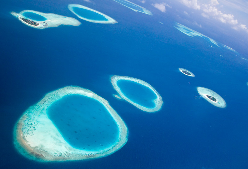 The entire country is made up of low-laying coral atolls like these.  Some islands are given over completely to tourist resorts (like the one in the upper left).<br /> <br /> Location: Over the northern archipelago, Maldives<br /> <br /> Lens used: 28-135mm f3.5-5.6 IS