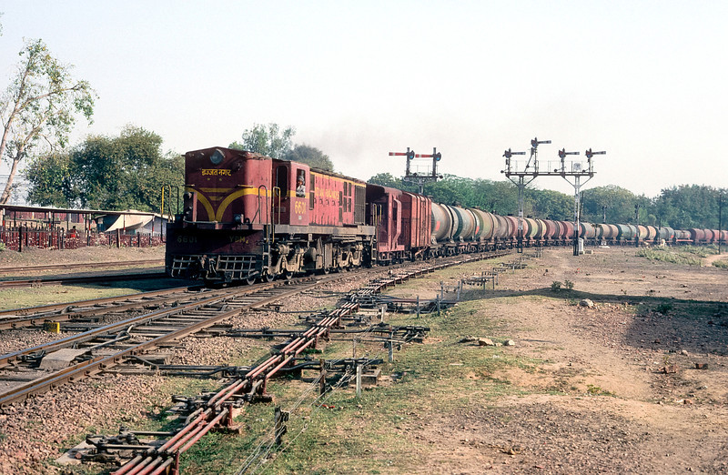 With a long rake of tank wagons YDM4 6601 blasts through Mathura Junction on 9 March 1992