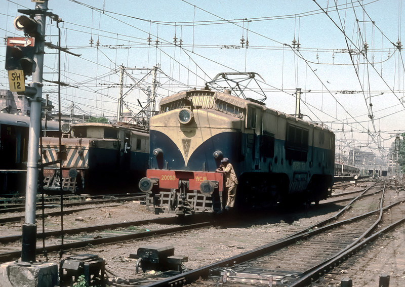 A home built version of the DC electrics supplied from Britain, WCM5 20098 passes the elderly WCG1 in the yard at Bombay VT on 6 March 1992