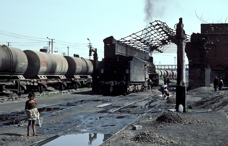 The locals look on as WG10106 simmers alongside the petrol and kerosene tankers within the walls (no roof!) of the old shed at Patna Junction on 23 February 1992