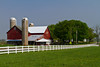 A red dairy barn and white fence near Nappanee, Indiana, USA.