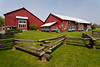 A rustic fence and red barns at the Amish Acres cultural village in Nappanee, Indiana, USA.