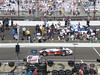 Cars through the decades driving past in pit lane