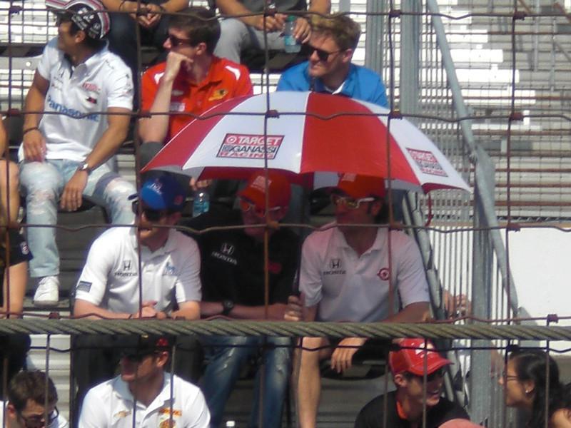 Dario Franchitti in white shirt on the right under umbrella