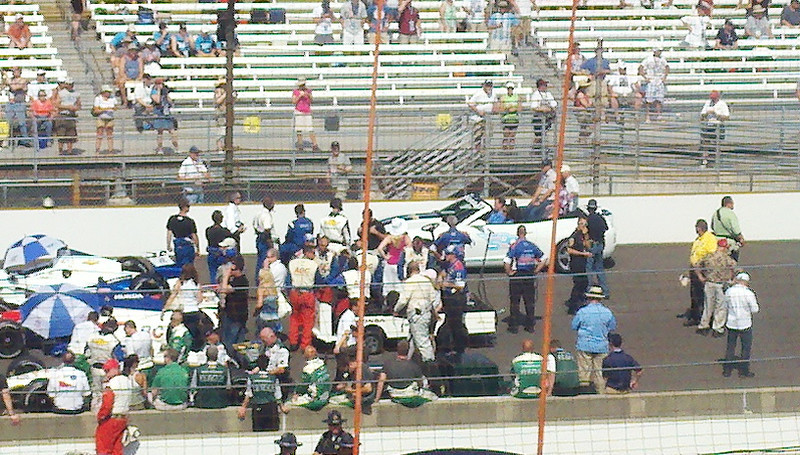 Cars gridded on track w/past winners in pace cars going by beyond.  Umbrellas were to keep the son off the cockpits.