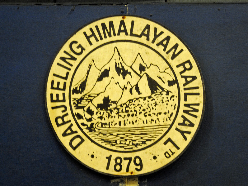 Welcome to the Darjeeling Himalayan Rly!  1879 DHR crest, Ghum, Fri 30 March 2012.  1879 saw the start of work on the 55 mile, 2ft gauge line from the hot plains of West Bengal to the cool Himalayan foothills close to Sikkim and India's borders with Nepal, China and Bhutan.  It opened to Darjeeling in 1881.  The line climbs to a summit of 7407 ft at Ghum via six switchback reverses, three loops and many, many tortuous cuirves.  The ruling gradient, allowing for curvature,  is estimated to be 1 in 16.  The DHR's trademark is its fleet of B class 0-4-0Ts introduced in 1889.  Many are still in service, though there are now four diesels as well.  The DHR became a UNESCO World Heritage Site in 1999, and is run by the North East Frontier Rly zone of  Indian Rlys, hence 'NF' on the B class bunkers..