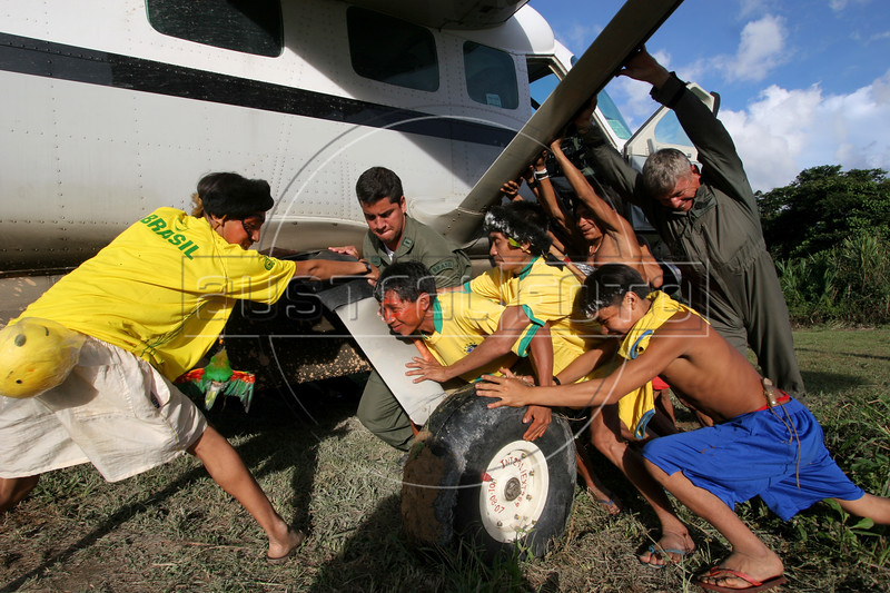 Brazilian Air Force (FAB) Col. Jose Hugo Volkmer, far right, gets help from Yanomami tribesmen in pushing a plane off of an airstrip on the Yanomami reserve in Roraima state, Brazil. Health conditions for the Yanomami have improved ever since the beginning of relief missions by the FAB. The FAB uses its infrastructure and know-how to promote a three part policy for the remote Amazon region near the Venezuela and Guyana borders: To show a presence of state in the inaccessible area, by taking medical personnel to those areas and finally, to train pilots in during real-life relief missions in an extreme environment. The increased presence in the area is, in part, to combat drug trafficking from Colombia into Brazil through Venezuela, which has increased after borders areas with Colombia have become more secure. Some say it may also be a reaction to Venezuela's recent acquisition of Russian-made helicopters and fighter jets. (Australfoto/Douglas Engle)