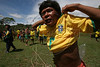 A Yanomami indigenous man puts on a Brazil Football jersey near an airstrip on the Yanomami reserve in Roraima state, Brazil. Health conditions for the Yanomami have improved ever since the beginning of relief missions by the FAB. The FAB uses its infrastructure and know-how to promote a three part policy for the remote Amazon region near the Venezuela and Guyana borders: To show a presence of state in the inaccessible area, by taking medical personnel to those areas and finally, to train pilots in during real-life relief missions in an extreme environment. The increased presence in the area is, in part, to combat drug trafficking from Colombia into Brazil through Venezuela, which has increased after borders areas with Colombia have become more secure. Some say it may also be a reaction to Venezuela's recent acquisition of Russian-made helicopters and fighter jets. (Australfoto/Douglas Engle)