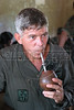"""Brazilian Air Force (FAB) Col. Jose Hugo Volkmer sips a """"chimarrao,"""" a drink typical of southern Brazil, during a brief medical stop by the FAB in the Ingariko community of Manalai in a remote area of Roraima state, Brazil. According to Volkmer, the Brazilian Air force has adopted a three part policy for the remote Amazon region near the Venezuela and Guyana borders: To show a presence of state in the inaccessible area, by taking medical personnel to those areas and finally, to train pilots in during real-life relief missions in an extreme environment. The increased presence in the area is, in part, to combat drug trafficking from Colombia into Brazil through Venezuela, which has increased after borders areas with Colombia have become more secure. Some say it may also be a reaction to Venezuela's recent acquisition of Russian-made helicopters and fighter jets. (Australfoto/Douglas Engle)"""