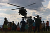 Onlookers of the Ingariko community of Manalai watch a Brazilian Air Force (FAB) Blackhawk helicopter take off during a relief mission in the remote area of Roraima state, Brazil. The Brazilian Air force has adopted a three part policy for the remote Amazon region near the Venezuela and Guyana borders: To show a presence of state in the inaccessible area, by taking medical personnel to those areas and finally, to train pilots in during real-life relief missions in an extreme environment. The increased presence in the area is, in part, to combat drug trafficking from Colombia into Brazil through Venezuela, which has increased after borders areas with Colombia have become more secure. Some say it may also be a reaction to Venezuela's recent acquisition of Russian-made helicopters and fighter jets. (Australfoto/Douglas Engle)