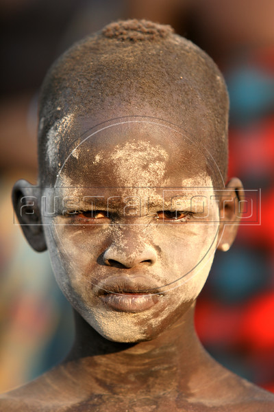 A Dinka boy at a cattle camp near Mapuordit in the semi-autonomous south Sudan, Nov. 23, 2005. The Dinka is one of the largest tribes of south Sudan, inhabiting the swamplands of the Bahr el Ghazal region of the Nile basin. They are mainly pastoral people, relying on cattle herding at riverside camps in the dry season and growing millet (Anyanjang) in fixed settlements during the rainy season. Among well-known Dinka are supermodel Alek Wek, former NBA player Manute Bol, one of the two tallest players in the league's history and current NBA player Lual Deng. A Jan. 2005 peace accord ended a 21 year civil war in Sudan, in which some 1.5 million were killed. The wat pitted the Muslim-dominated government in Khartoum against the mainly Christian and anamist south. The peace deal includes wealth and power-sharing arrangements, created a national unity government in Khartoum and gives southern Sudan a six-year period of autonomy after which it will hold a referendum on secession. (Douglas Engle/Australfoto)