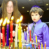 Sam Schantz, Lauren Kiefer and Michael Lack of Plattsburgh light their menorahs at the annual celebration at Temple Beth Israel in Plattsburgh. Hanukkah, or the Festival of Lights, took place from Dec. 21 through 29. The holiday commemorates the miracle of oil and the rededication of the Holy Temple in Jerusalem.<br><br>(Staff Photo/Kelli Catana)