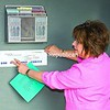 The information kiosk at the Port Henry Public Boat Launch has been repainted, repaired and restocked with maps and brochures for visitors. Putting up a waterfront map is Barbara Brassard of the Lake Champlain Regional Marketing Committee.<br><br>(Staff Photo/Lohr McKinstry)