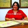 Clinton County Historian Anastasia Pratt opens an atlas in her office last week.<br><br>(P-R Photo/Rachel Moore)