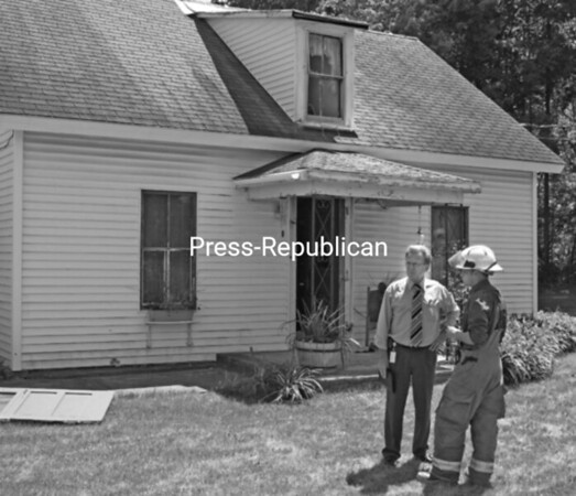 Essex County Emergency Services Director Raymond Thatcher (left) confers with Fire Investigator Joseph Norton at a house fire Thursday afternoon in Ticonderoga. A two-story house on Route 9N/22 was moderately damaged by a fire that began on the second floor.<br><br>(Staff Photo/Lohr McKinstry)