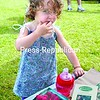 Zarela Gulli, 2, of Keene enjoys fresh raspberries while her mom, Tammy Loewy, sells produce at her Green Goddess Natural Foods booth at the farmers market in Keene Valley. <br><br>(Staff Photo/Alvin Reiner)