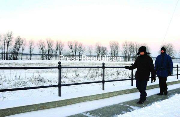 Jean-Francois Bordin (left), who is from France, steadies himself Tuesday as he walks on an icy sidewalk with Guy Morissette of Montreal near the Plattsburgh Boat Basin. The wind chill today will be as low as minus-11 degrees, with 5-to-8-mph winds, according to the National Weather Service.<br><br>(Staff Photo/Kelli Catana)