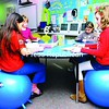 """Isabel Yu, 8; Amelie Arguelles, 9; Amelia Carter-Kelly, 8; and Morgan Keable, 8, sit on WittFitt balls during their third-grade class with Catherine Hite. Momot Elementary replaced chairs in first grade, second grade, third grade and special education classrooms with the WittFitt balls. The balls improve posture, concentration and focus. """"I don't want to go back to a real chair again,"""" Arguelles said.<br><br>(Staff Photo/Kelli Catana)"""