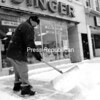 Owen Wood, co-owner of the Singer Shop at 66 Margaret St., Plattsburgh, shovels the storefront sidewalk. A City of Plattsburgh law requires property owners — both business and residential — to keep sidewalks clear.<br><br>(Staff Photo/Kelli Catana)
