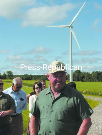 One of the seven turbines (left) erected by Noble Environmental Power on Hy-View Acres in Chateaugay stands behind farm owner Doug Malette. He and his son, Rod, turned the 600-acre potato farm into a viable cash-crop operation. The dairy herd on the Norm and Vicky Shipman farm in Burke (top and bottom right) has more freedom, and the cows can feel as if they are outdoors without having to brave the harsh North Country weather. The facility was one of four stops on the recent Franklin County Farm Bureau tour. <br><br>(Staff Photo/Denise A. Raymo)