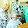 Intensive Care Unit registered nurse Susan Windover-Drurey listens to Charles Moore's lungs for sound while Jennifer Kanaly checks his I.V. pump.<br><br>(Staff Photo/Kelli Catana)