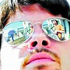 Dan Gallagher is reflected in Dave Slominski's sunglasses as they play music outside in Plattsburgh during the warm weather Saturday.<br><br>(P-R Photo/Michael Betts)