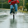 Rain does not stop Jordan Bashaw from riding his bike toward the Samuel de Champlain Monument in Plattsburgh to go fishing on the shores of Lake Champlain. Bashaw was making his first angling outing of the year to see if the wet weather would entice fish.<br><br>(P-R Photo/Rachel Moore)