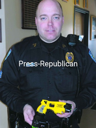 Malone Village Police Department Sgt. Brian Smith holds one of the two Taser X26 model electric-control devices the department recently purchased. When activated, it fires a probe into an unruly person's body and delivers a five-second jolt of 50,000 volts of electricity in hopes of incapacitating the suspect.<br><br>(Staff Photo/Denise A. Raymo)