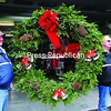 A 4-foot-high evergreen wreath is carried by Dave Martelle (left) and Ken McLaughlin of the Saranac Lake Fire Department. About a dozen volunteer firefighters were on hand to decorate the Fire Station on Broadway.<br><br>(P-R Photo/Jack LaDuke)