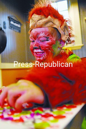 Five-year-old Trent Trahan of Chazy browses through a sheet of stickers as he decorates a Halloween craft at the Spooktacular Celebration at The Station Cafe in Chazy. Children were treated to free face painting, special Halloween arts and crafts and festive snacks at the family friendly event.<br><br>(P-R Photo/Rachel Moore)