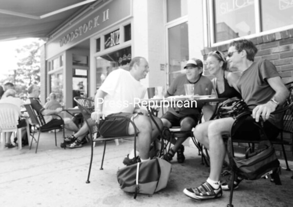 Eric Campeau of Montreal, Rene Girard of Sherbrooke, Maryse Racine of Montreal and Dominic Racine of Montreal sit in the area outside Pizza Bono and Woodstock II in Plattsburgh to have lunch. According to Campeau, the roads he traveled in the North Country are very good for cycling.<br><br>(Staff Photo/Kelli Catana)