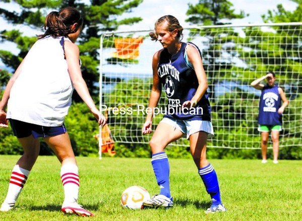 Clinton Community College's Morgan Roussy (right) tries to move the ball around teammate Molly Bowen during women's soccer practice Friday.<br><br>(P-R Photo/Gabe Dickens)