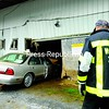 A woman was injured and calves died Tuesday around noon when her car ended up 25 feet into one of the barns at North Country Livestock Exchange in Chazy. West Chazy volunteer firefighter Rick Morrison stood ready to douse the vehicle with water while Pilon Transportation Co. towed it out of the barn.<br><br>(Staff Photo/Kelli Catana)