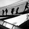 """Youngsters are silhouetted against the sky as they play """"Raiders"""" at the Essex County Fair Saturday. Participants climb and run along suspension bridges, then escape through a chute.<br><br>(Staff Photo/Alvin Reiner)"""
