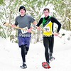 Jordan Peters (left) and Kyle Dash, two Paul Smith's College students whose moms clearly never taught them not to run with sharp objects, charge to the starting line of Saturday's Jingle Bell 5K Snowshoe Race after doing a quick trail cleanup. About an hour before the race was to begin a tree toppled onto the trail, blocking the race course. An appeal went out for axes, and of course there is never a shortage of woodsmen at PSC. The event got moving after only a five-minute delay, thanks to the efforts of Peters and Dash. Story, more photos, Page B3.  <br><br>(P-R Photo/Pat Hendrick)