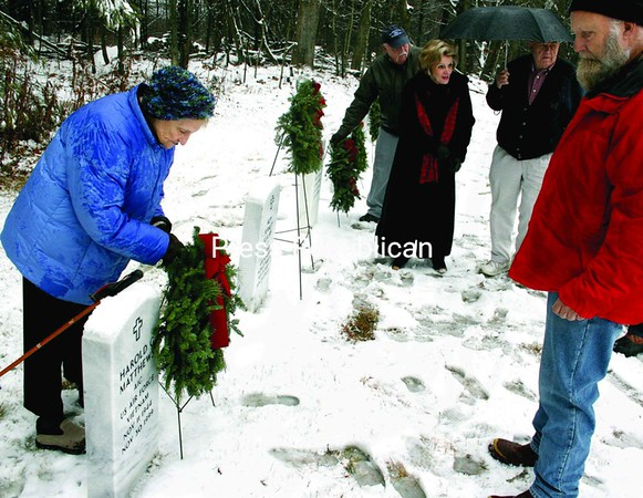 "In spite of the snow, sleet and rain Sunday, about 25 citizens gathered at the Essex County Cemetery near Wadhams to place wreaths at the monuments to those who have died. ""In this season when friends and family traditionally get together, many of us want to remember those military service veterans who have passed on and can no longer be with us physically,"" Elizabethtown-Lewis American Legion Post Commander Newman Tryon said in his address to the crowd. Locally, more than $300 was raised to cover the cost of the wreaths. The brief ceremony closed with a prayer by acting chaplain Betty Light, followed by Kim Matthews playing ""Amazing Grace."" Egglefield Ford provided cider and other refreshments at the dealership.<br><br>(Staff Photo/Alvin Reiner)"