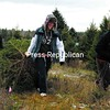 Don Covel watches as Erica Erickson, accompanied by Missy LaClair, drags their freshly cut Christmas tree back to the main building of the Covel Tree Farm and Nursery in Peru. There, it was shaken and bundled up for the ride home to Keeseville.<br><br>(P-R Photo/Gabe Dickens)