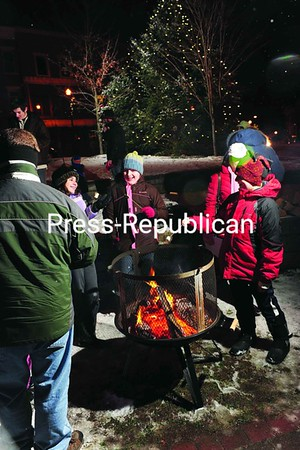 Scores of people gathered in Saranac Lake Saturday night to take part in a Christmas-tree lighting (background), caroling and marshmallow-roasting event. A group of local women volunteered to organize the Home for the Holidays celebration that attracted about 100 people.<br><br>(P-R Photo/Jack LaDuke)
