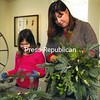 Plattsburgh residents Donna Kirkey and her daughter, Caroline, 8, create kissing balls at Alice T. Miner Museum in Chazy. Participants in the workshop used a collection of evergreen branches, holly, eucalyptus, grasses, bows and ribbons and other materials to create the holiday decorations, which are stuck into a potato attached to a coat hanger. <br><br>(P-R Photo/Gabe Dickens)